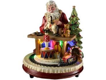 Dekorationsfigur Weihnachtsmann am Tisch mit Zug